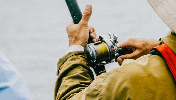 Man fishing with conventional reel and the best fishing line