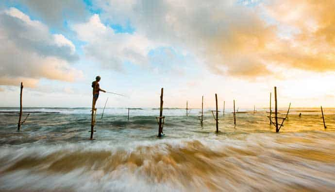 Man surf fishing on a wooden pole