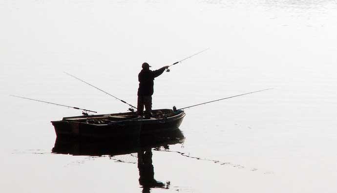 Man fishing for catfish on boat