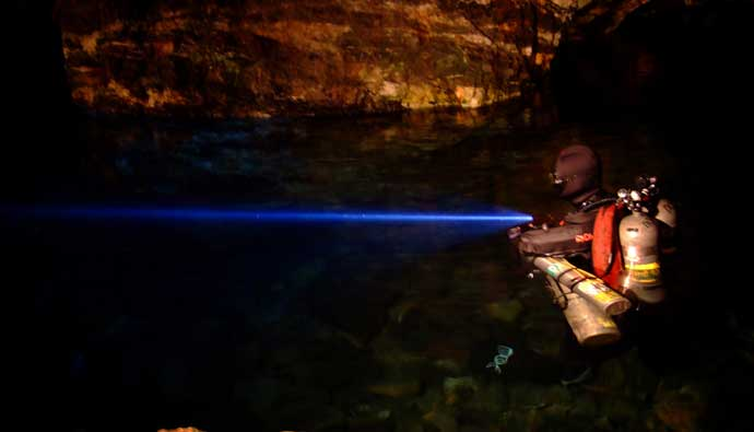 Scuba diver using a dive light in a cave