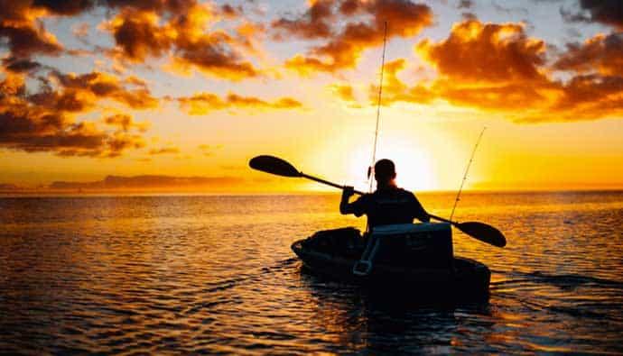 Man at sunset fishing on his ocean kayak