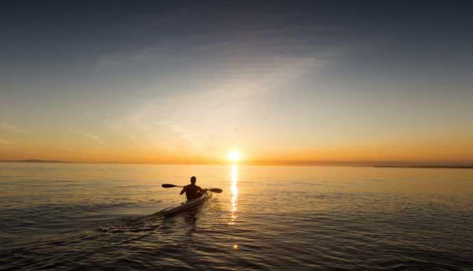 Man in an ocean kayaking at sunset