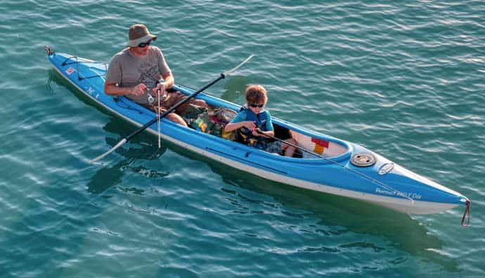 Dad and son fishing on an ocean kayak