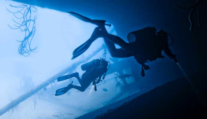 Two scuba divers using an underwater flashlight