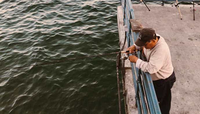 Man pier fishing with a saltwater fishing rod