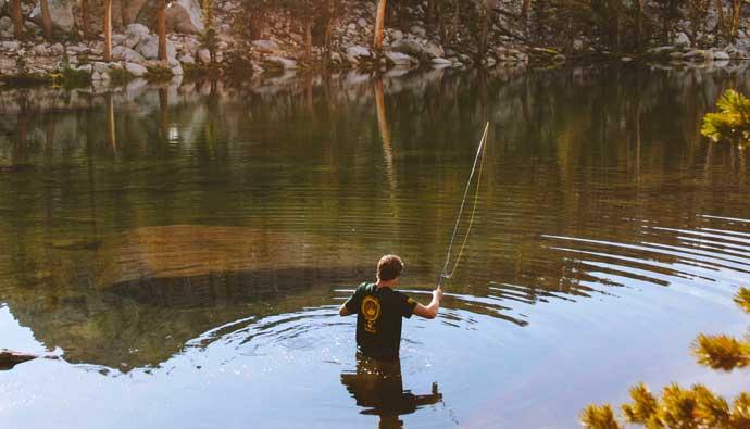 Man in lake finesse fishing