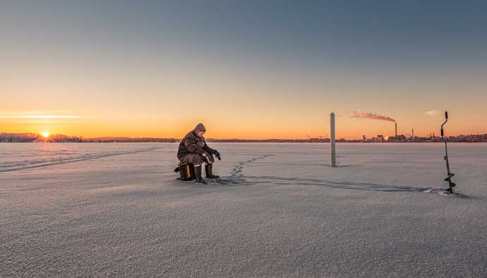 Man on lake with ice fishing tips