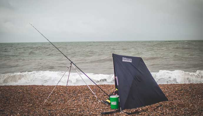 man in tent while beach fishing
