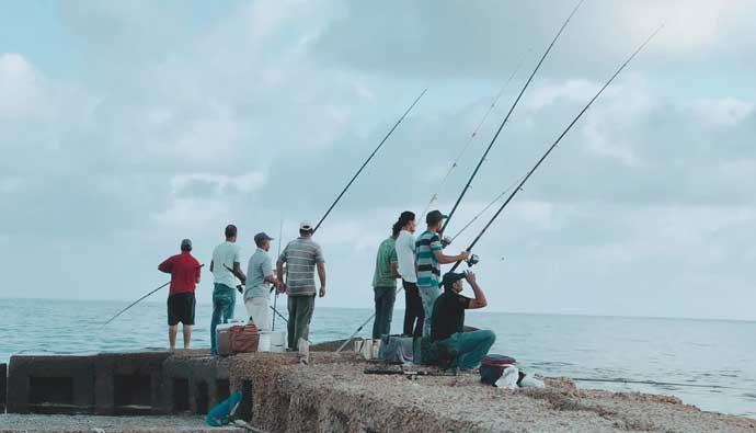 men surf fishing the jetty