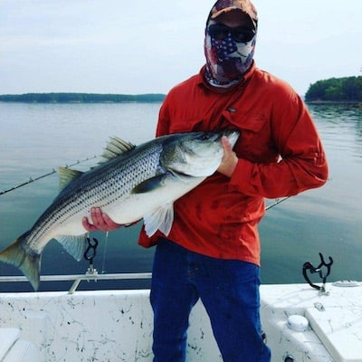 the coach with a striped bass
