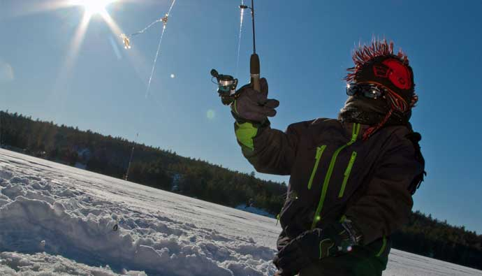 man ice fishing with a rod and reel
