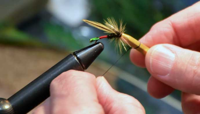 man tying a fly for fishing